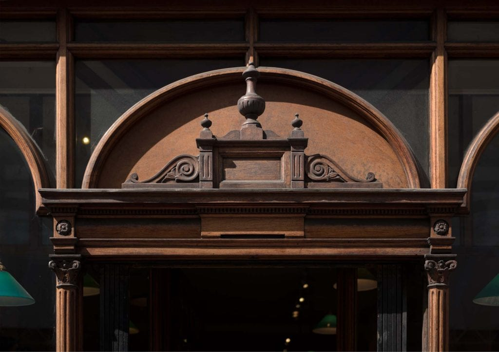 Pediment over the entrance to Daunt Books, 83 Marylebone High Street. Photographed by Chris Redgrave © Historic England.
