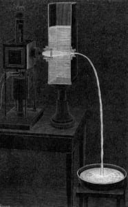 """In the above illustration by Jean-Daniel Colladon, water comes out of a short spout on the watertank and then falls through open air, as in a fountain. The device on the illustration's lefthand side produces light and directs a beam of light into the watertank. The demonstration of this """"light fountain"""" needs to be done in a darkened room to see the effect."""
