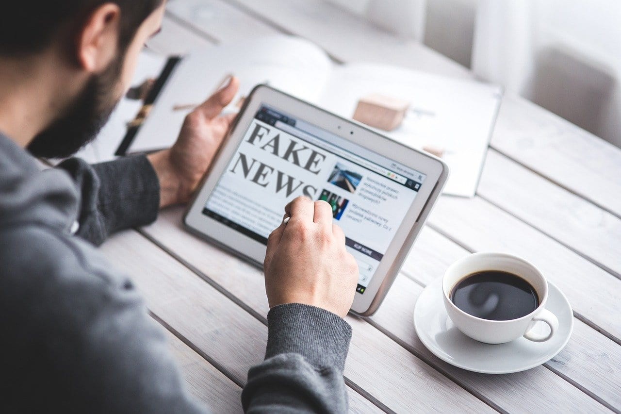 Man using tablet to view fake news website