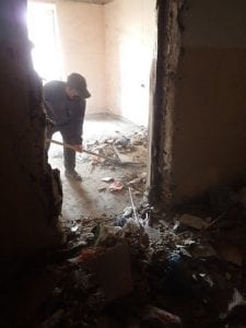 Image 4: An apartment owner cleans out the accumulated and decayed rubbish of an empty apartment in the lower floor of his building.