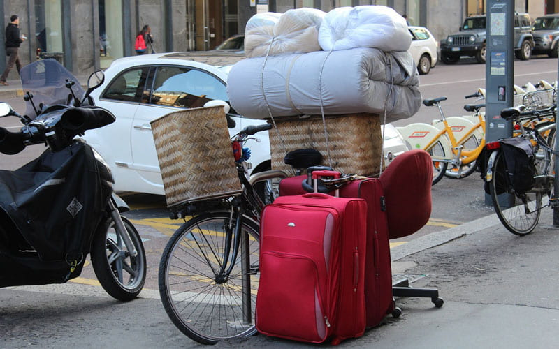 Suitcase, bedding and baskets placed on a bike