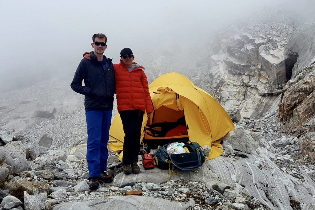 A doctor and nurse standing on a mountain, with a medic-tent in the background.
