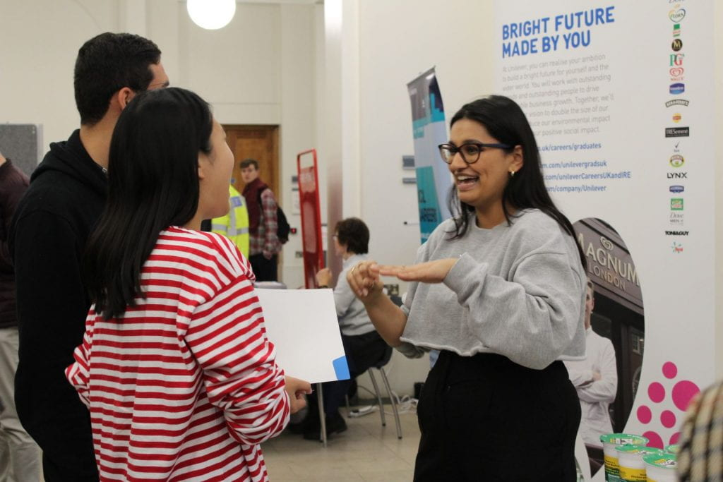 Two student talking to an employer at a careers fair