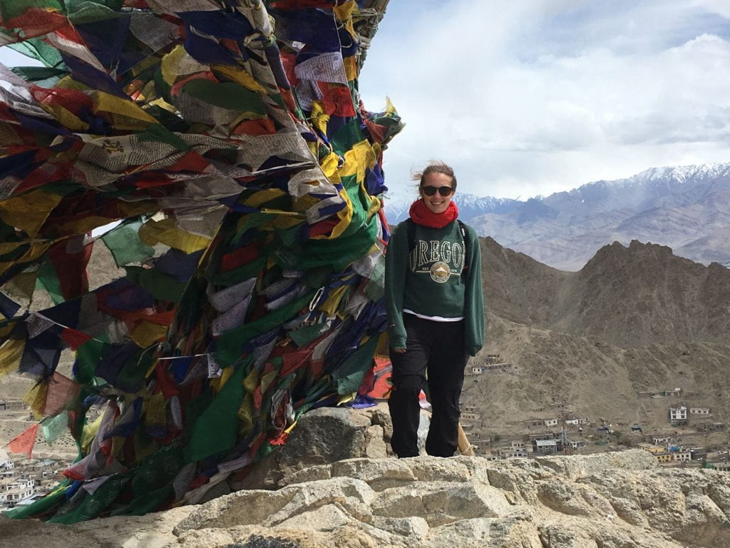 A student standing on top of a mountain with the mountain region behind her and many colourful flags to her left
