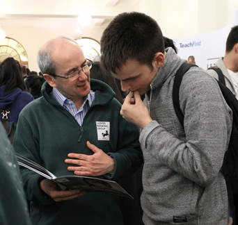 An employer talking to a student at a careers fair