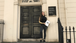 Young woman student standing in front of the door of a UCL building