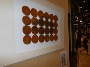 artwork on wall consisting of nails hammered into symmetrical discs of waffle