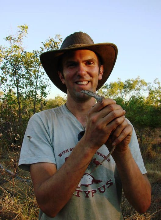 A zoologist holding a monitor lizard with a very silly hat on