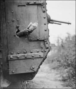 A message-carrying pigeon being released from a port-hole in the side of a British tank, near Albert, France.