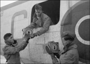 Crewmen of Consolidated Liberator of No. 53 Squadron RAF handling carriers containing homing pigeons