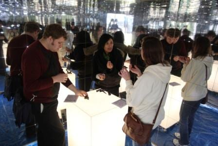 People discussing objects and subjects in the mirrored outreach box called The Thing Is