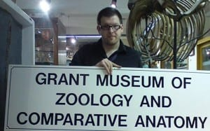 Mark Carnall, Curator of the Grant MUseum of Zoology holding the old museum sign