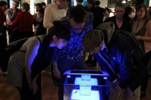 """Examining a piece of DNA, the """"Public BioBrick"""" at the 2012 """"Right or Risk?"""" exhibition"""