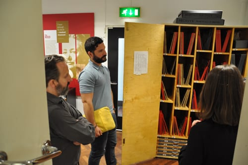 Language specialists looking into an open cupboard filled with papyri