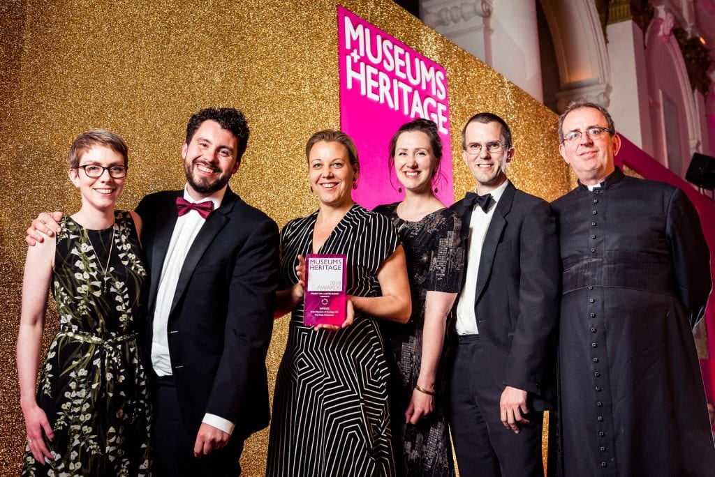Colour photo of six people standing in a row in front of a glittery wall. The woman in the middle is holding a pink award.
