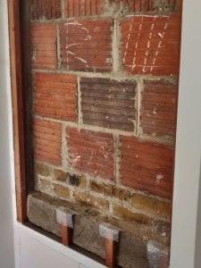 Rectangle cut out of a wall to reveal red brickwork