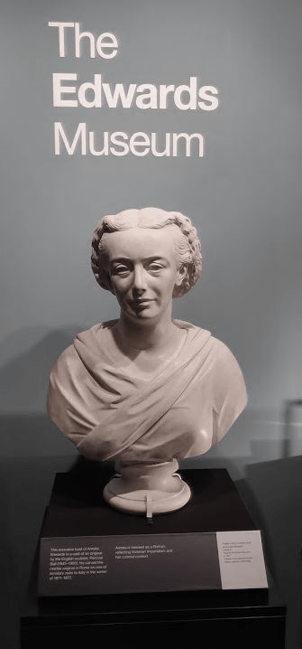Bust of Amelia Edwards on a plinth in gallery