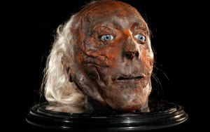 Dried, preserved human head with white hair, red-brown skin and blue glass eyes