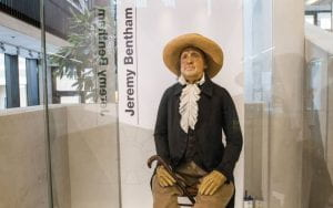 Jeremy Bentham's Auto-Icon with a waxwork head, dressed in his original 19th century clothes, sitting on a wooden chair inside a glass museum display case