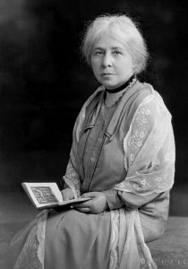 Black and white image of Margret Murray wearing a lace shawl, seated and holding a book