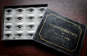 Black metal box containing 16 glass eyes of different colours set into an aluminium backing