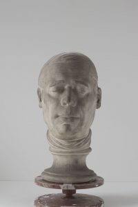 Plaster cast of a man's head. His eyes are closed an he is wearing a neck scarf.