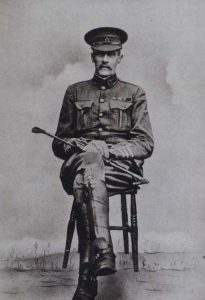 Black and white image of Charles Stoneham in military uniform sitting on a wooden chair holding a riding crop
