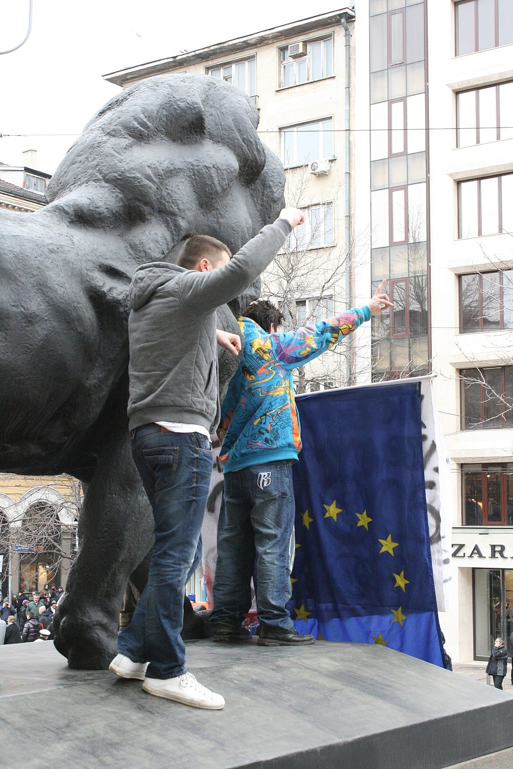 Protesters in Sofia standing on statue of a lion wave EU flag