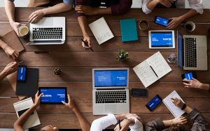 aerial view of laptops and mobile devices on a table with people sitting around them
