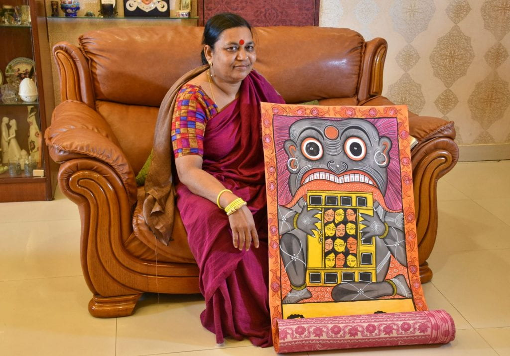 Swarna Chitrakar sits on a couch with a highlt decorative scroll painting