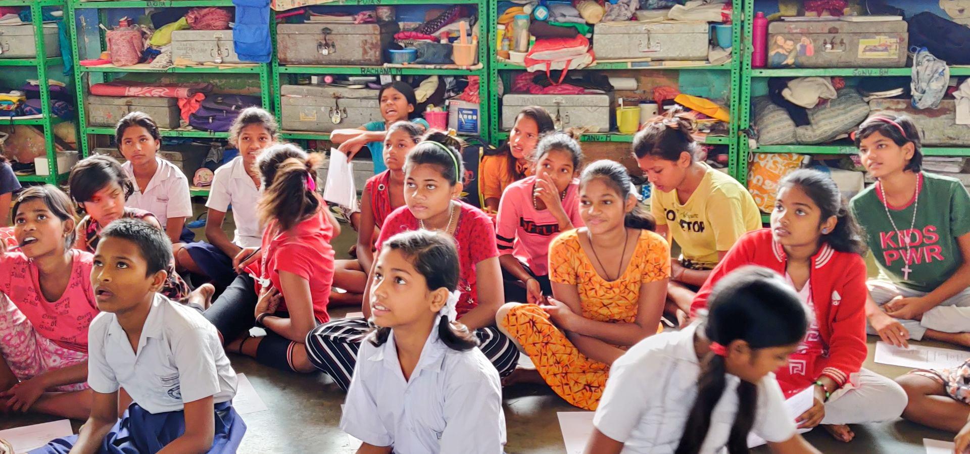 Children sitting cross-legged on the classroom floor, listening