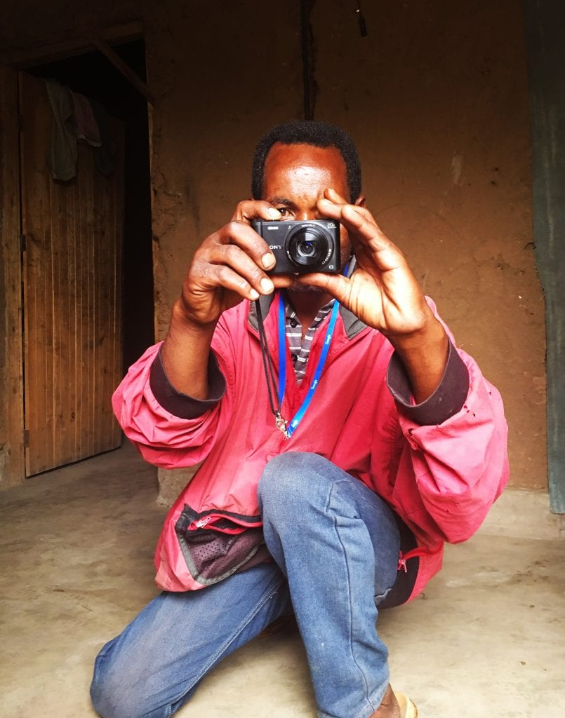man crouching, face obscured by camera