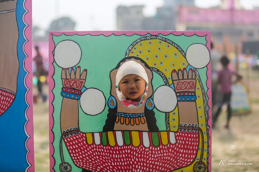 Child has photo taken in a hand-painted face-in-hole board