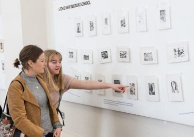 Image of two students pointing to their work on display at the Make an Impression Exhibition launch.
