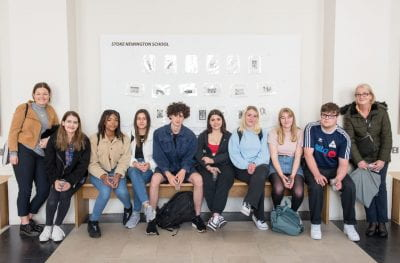 Image of students posing in front of their prints on display for the Make an Impression exhibition in the North Cloisters