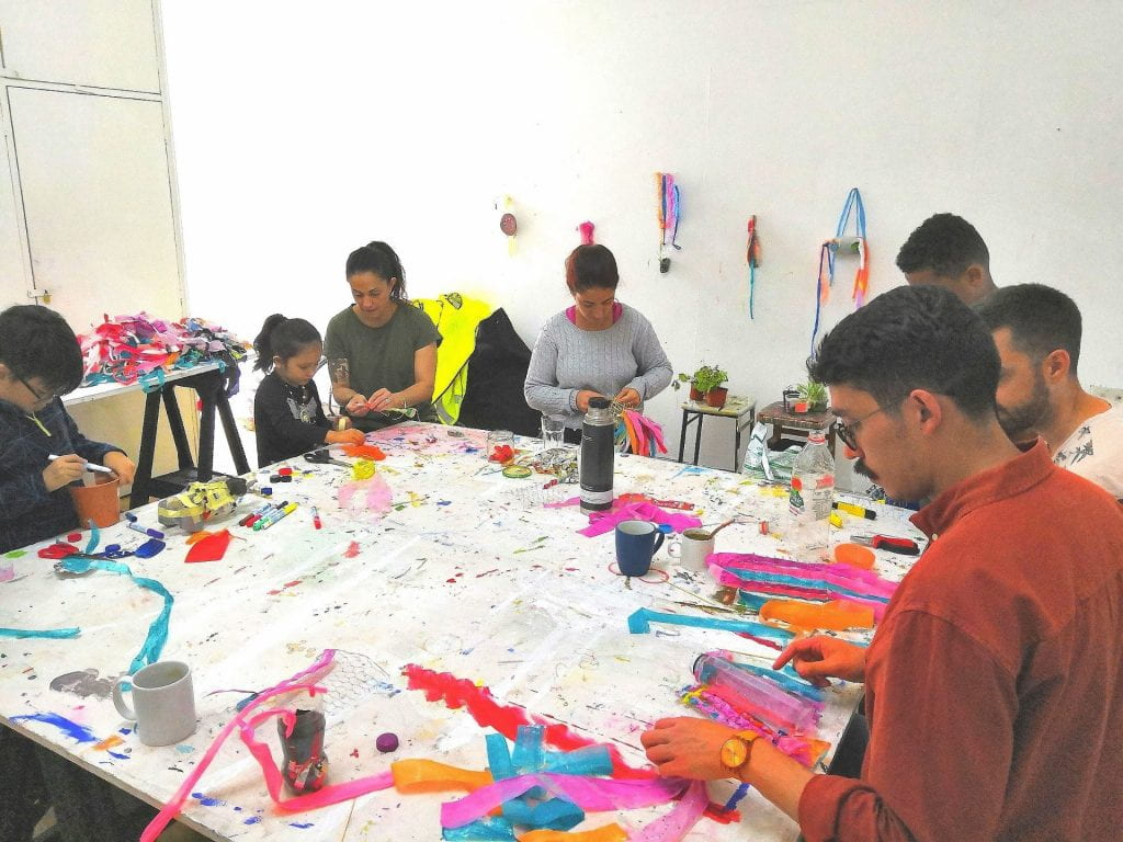 Workshop participants creating mobiles made from plastic pollution
