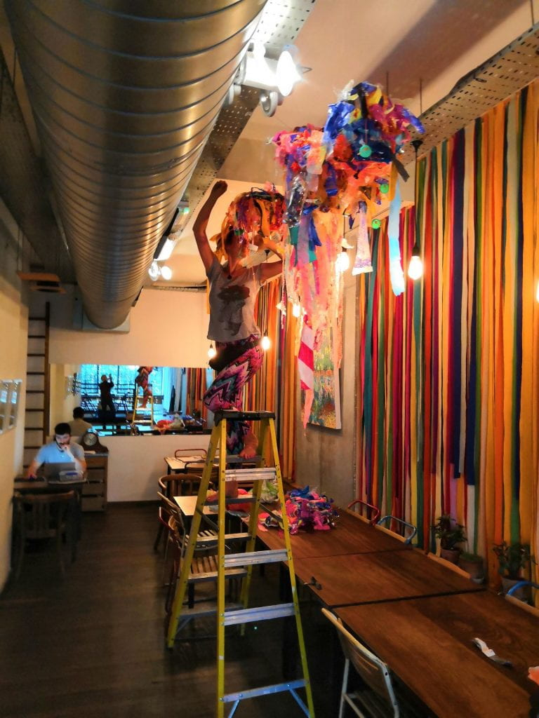Camilla Brendon hangs plastic scultpures in her studio
