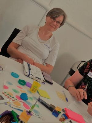Here's Annegret at our event in July. She's at a table ready for co-creation activities with notebooks, Play-Doh, stickers, and Lego.