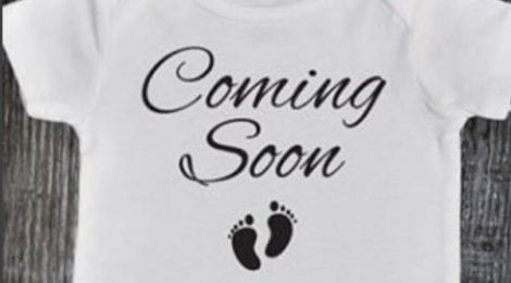 A baby grow with coming soon and a pair of baby feet on it