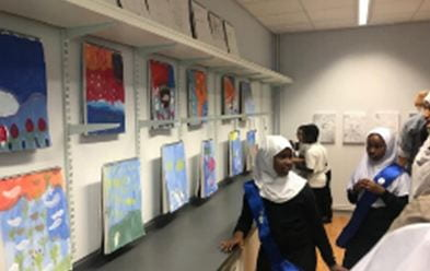 Pupil engaging visitors in a tour of the painted paper tapestry.
