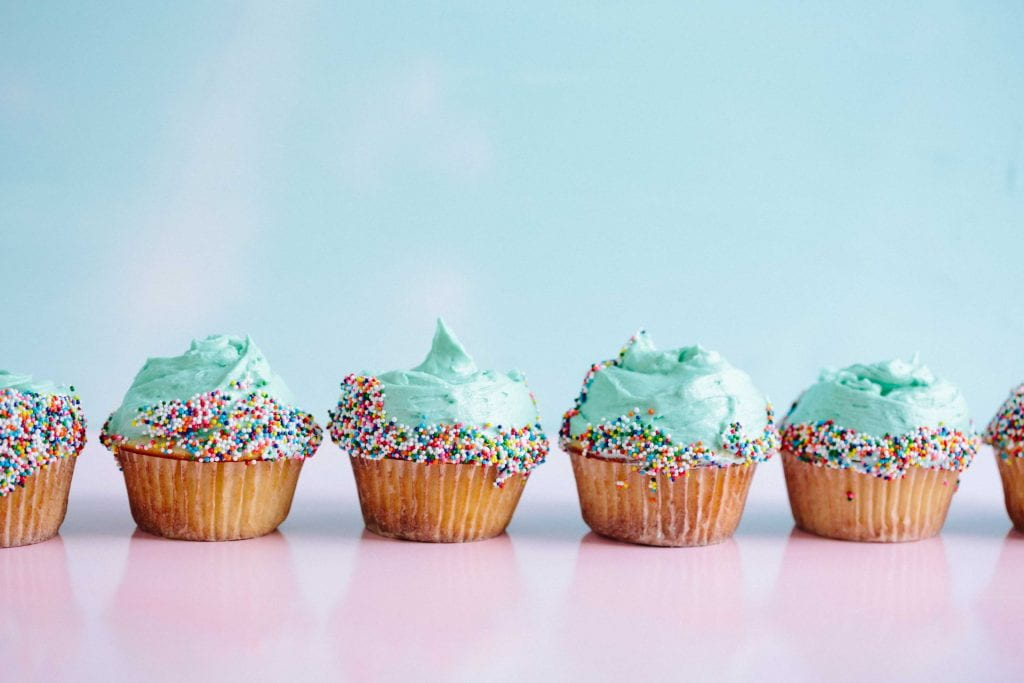 A row of cupcakes with mint green icing and multi coloured sprinkles