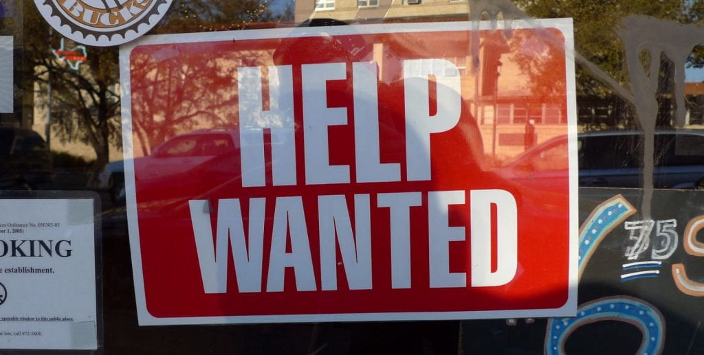 Red and white sign that says 'Help Wanted'
