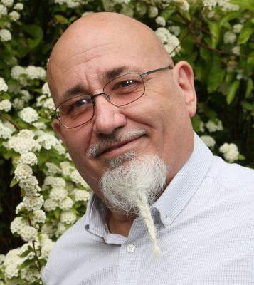 Jon Adams headshot, bald man with glasses and white goatee