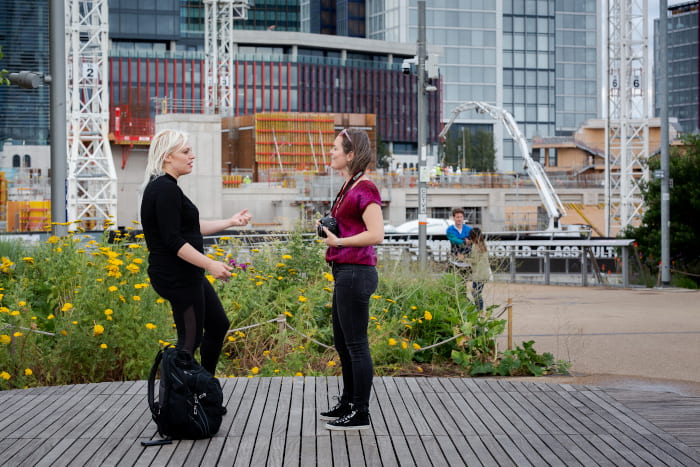 Two women viewed side on speaking, with large construction work behind them