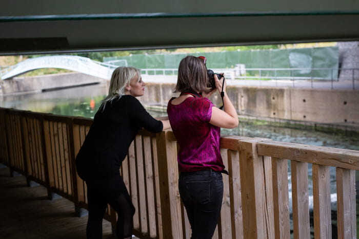 view from behind of two women lean on a fence looking out over a canal, one looking into a camera