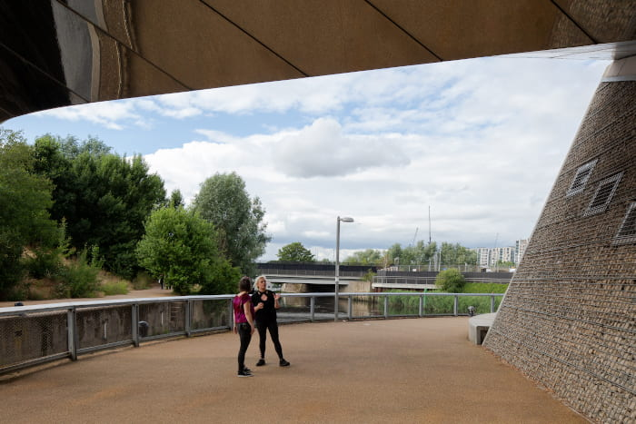 Georgia and Briony converse under a bridge in the Olympic Park