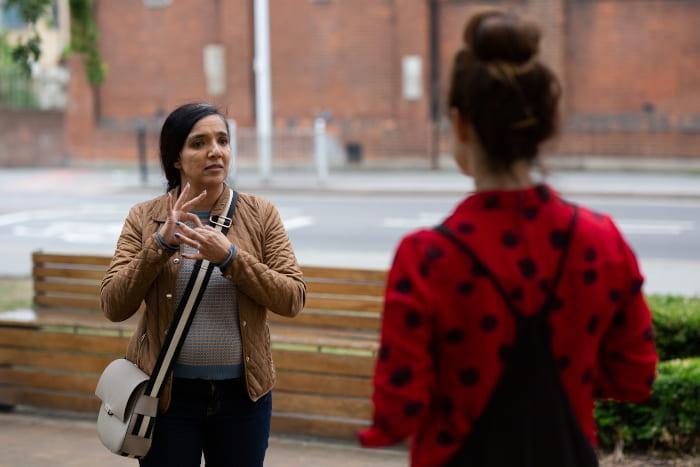 Artist Rubbena talks to her BSL interpreter outside St Paul's Way Trust School