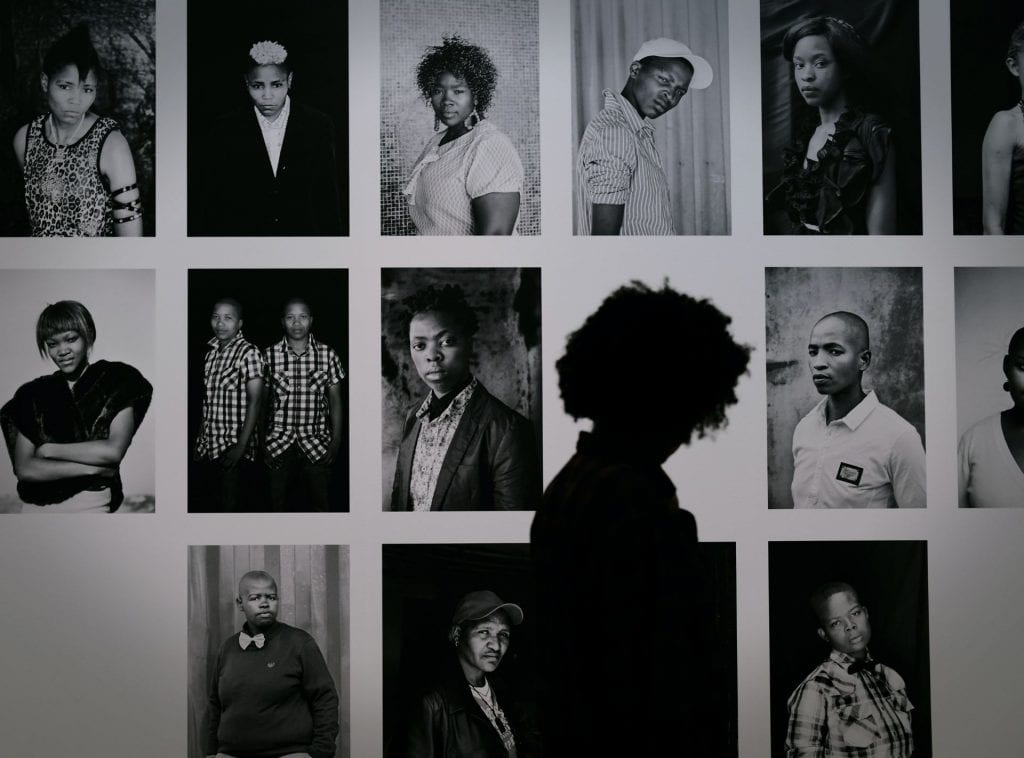 Collage of photographs of a diverse group of black people with a person walking past and looking at it