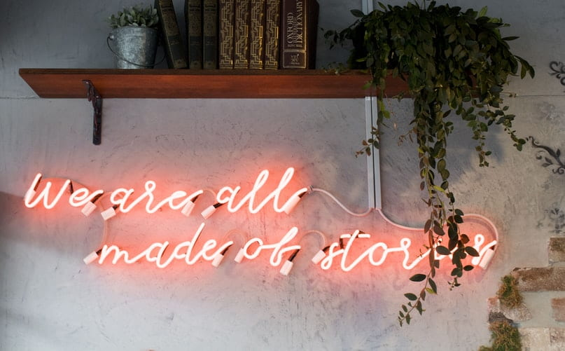 Shelf with books and a plant, above the words 'we are all made of stories' written in red lights