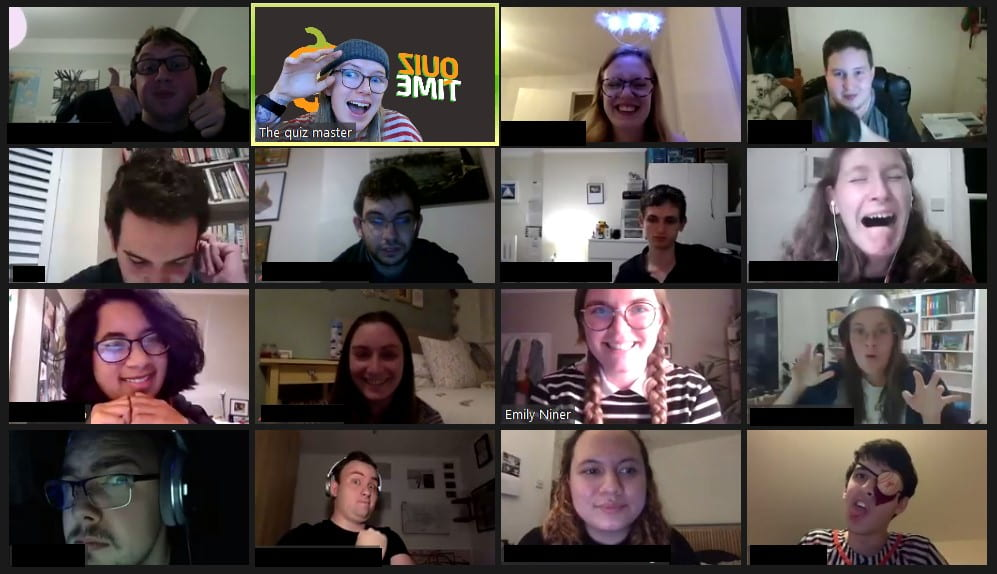 Screenshot from Halloween themed quiz party. 16 people on a video call, some are in halloween costume and some are not, people are smiling or grimacing at camera.